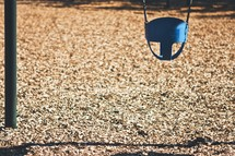 Child's bucket swing hanging over wood chips.