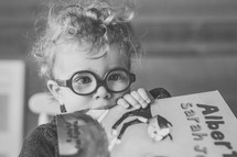 a child with glasses holding a book
