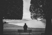 woman sitting on a park bench looking out over a waterway