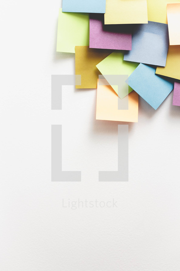 Colorful squares of paper in the corner of a white background.