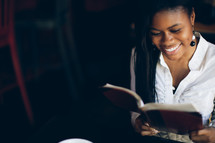 woman reading from a journal at a Bible study and smiling