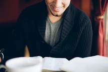 man reading from a Bible and smiling