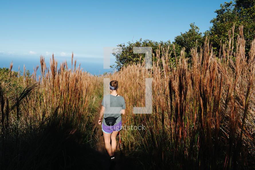 a woman hiking through tall brush