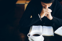 man with his hands held in prayer over a Bible