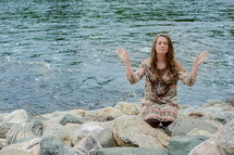 woman kneeling in prayer with her hands raised at the shore of a river