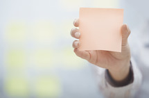 a woman holding up a blank sticky note
