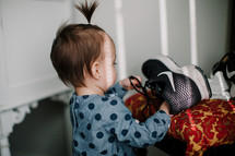 a toddler girl playing with dad's sneakers