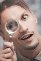 a man looking through a magnifying glass