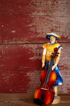 knit clothes on a figurine and violin