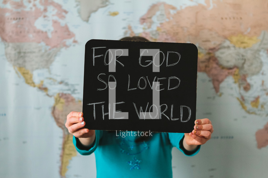 A girl in front of a world map holding a sign - For God so loved the world
