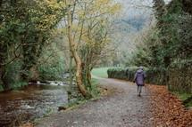 a woman walking on a path along a stream
