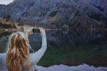a woman taking a picture of a lake with her phone