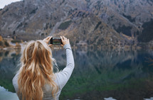 a woman taking a picture of a lake with her cellphone