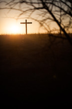 Cross on a hill at sunrise.