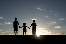 silhouettes of children holding hands outdoors