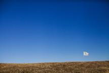White flag flying on grassy hilltop.