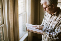 elderly man standing at a window reading a Bible by sunlight