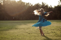 Girl twirling around outside in a field of grass.