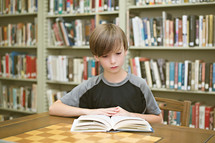 Boy reading a book on a table in a library.