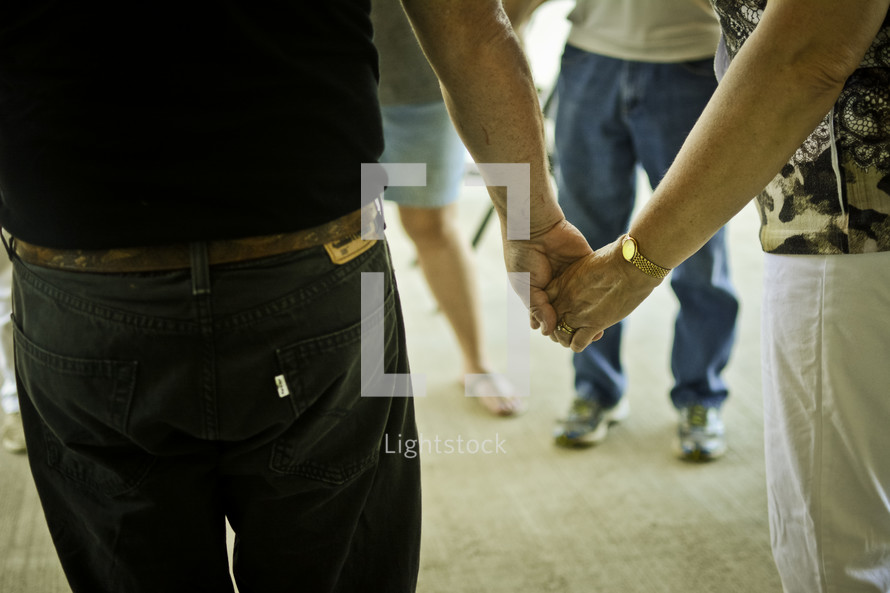 Men and women standing in a circle while holding hands.