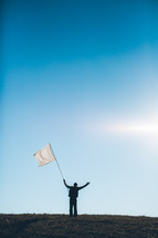 Silhouette of man waving white flag with arms raised on grassy hilltop.