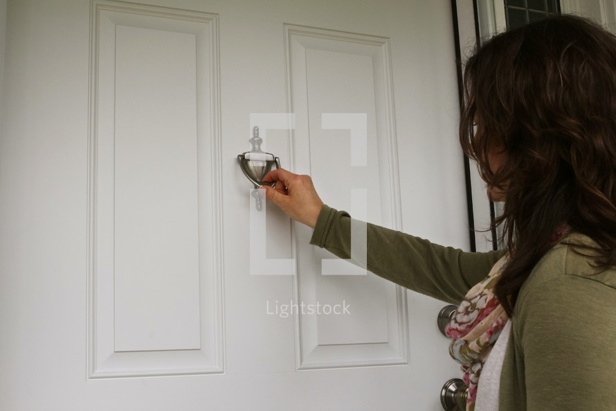a woman knocking on a front door