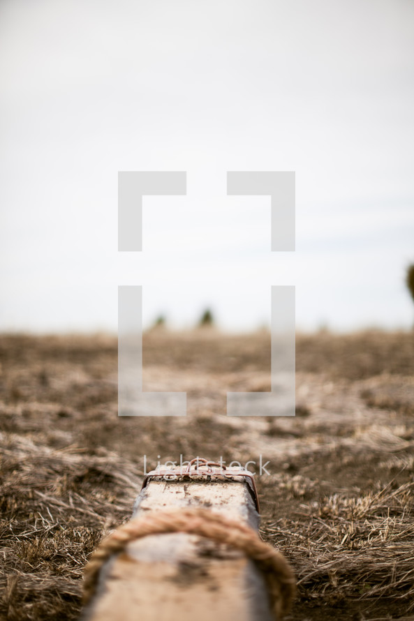 Wooden cross with ropes on it laying on the ground.