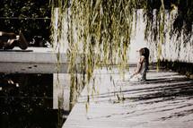 woman kneeling in prayer on a dock