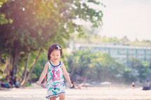 Little Asian girl playing on the beach.