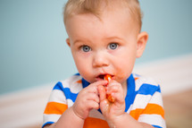 an infant boy eating a lollipop