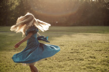 A girl with long blonde hair in a blue dress twirls in a field of grass.