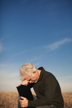 elderly man squatting in a field with his head bowed over a Bible in prayer