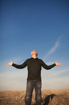 elderly man standing in a field with his arms outstretched in worship to God