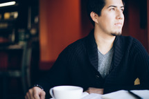 man with his head turned to the side sitting in front of a coffee mug and Bible