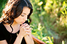 Latino woman with praying hands