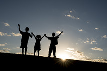 silhouettes of children holding raised hands
