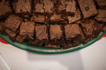 A pile of brownies on a plate.