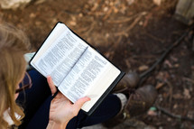 A woman sits and reads her Bible outdoors.