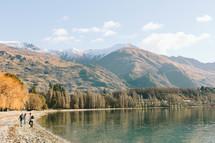 People walking beside a mountain lake.