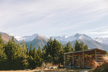 A shed full of firewood surrounded by trees and a mountain range.