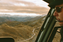 An airplane pilot flying over a mountain range.