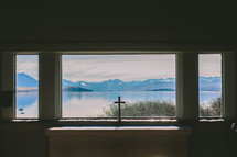 A cross in a window looking out at a lake and mountains.