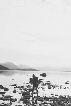 A girl walking on rocks on a lake's edge.