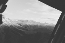 View of a mountain range from the window of an airplane.