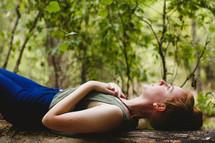 woman lying outdoors on a fallen tree