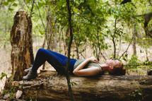 woman lying on a fallen tree in a forest