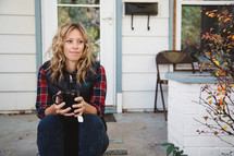 woman sitting on a stoop in front of her house holding a mug of tea