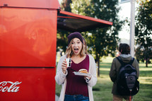 a woman getting food and drink from a food truck