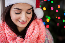 A smiling young woman wearing a santa hat