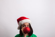woman in an ugly Christmas sweater and santa hat hiding behind a Christmas ornament